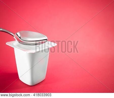 Yogurt Cup And Silver Spoon On Red Background, White Plastic Container With Yoghurt Cream, Fresh Dai