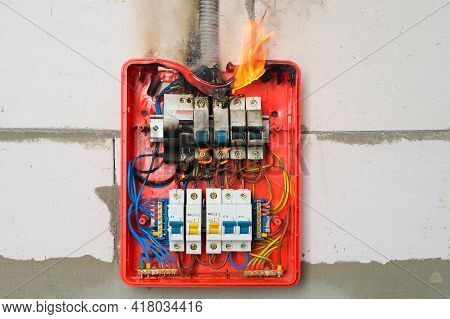 Burning Switchboard From Overload Or Short Circuit On Wall Close-up. Circuit Breakers On Fire And Sm