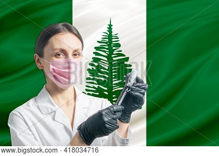 Girl Doctor Prepares Vaccination Against The Background Of The Norfolk Island Flag. Vaccination Conc