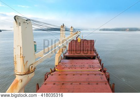 Close-up To Te Tower Cranes And Storage Hold Of A Cargo Ship In The Pacific Ocean In The Coast Of Ch