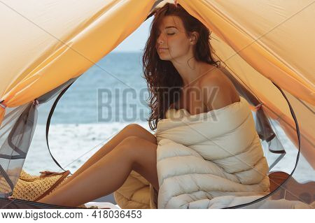 Naked Woman Sitting In A Sleeping Bag On The Beach. Gorgeous Girl With The Perfect Tanned Slim Body