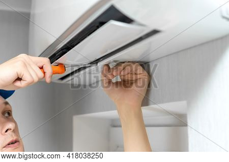 Close Up Of A Repairman's Hands With A Screwdriver Repairing An Air Conditioner On The Wall