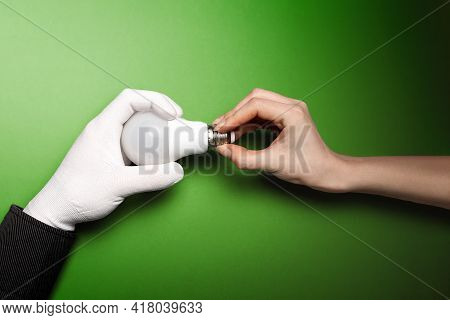 A Hand In A White Glove Takes A Light Bulb From The Other Hand. Green Background. International Inte