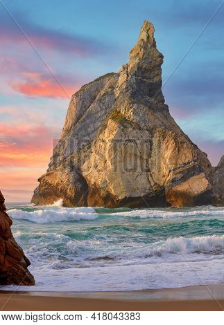Portugal Ursa Beach at atlantic coast of Atlantic Ocean with rocks and sunset sun waves and foam at sand of coastline picturesque landscape panorama.