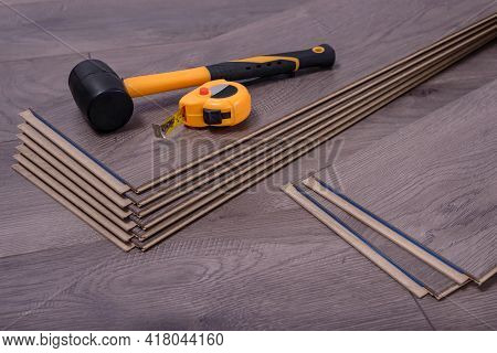 Hammer And Tape Measure On Laminate Panels, Carpenter Tools For Laying Laminate In The Room.