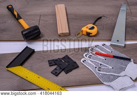 Equipment Or Tools To Install Laminate Floor. Hammer, Crowbar, Spacers, Mallet, Protective Gloves An