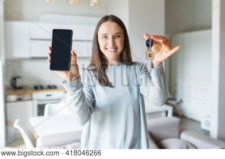 Selective Focus On A Smartphone With Blank Screen And Keys With Keyring In House Shape Woman Is Hold