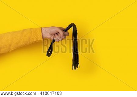 Leather Whip In Hand Over Yellow Background, Bdsm Accessories