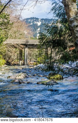 Denny Creek With Rocks On The Shore Flows Under A Bridge.