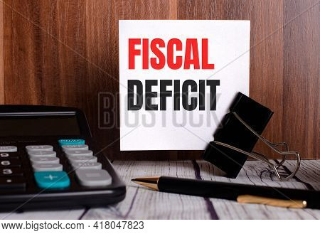 Fiscal Deficit Is Written On A White Card On A Wooden Background Next To A Calculator And Pen.