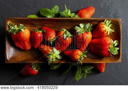 Delicious And Appetizing Red Strawberries (large Strawberries) On An Ebony Wood Tray And Mint Leaves