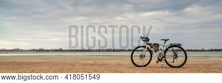 spring biking, touring or commuting - bicycle on a lake beach, Boyd Lake State Park in northern Colorado, panoramic banner