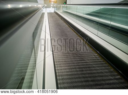 A Large Escalator Staircase In A Large Shopping Center On The Rise To The Top.