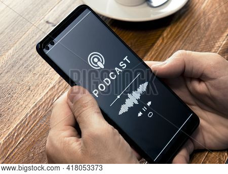 Close-up Of The Hands Of A Man In A Coffee Shop Holding A Smartphone With A Podcast Listening Applic