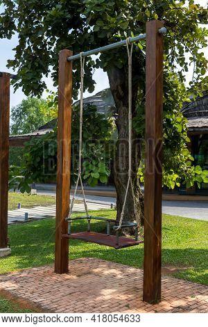 The Swings Hung Below The Brick Floor. Children Playground Ayunan Swing Hanging In Park Garden. Blan