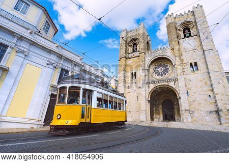 Lisbon City And Famous Yellow Tram 28 In Front Of Santa Maria Cathedral On A Sunny Summer Day. Trams