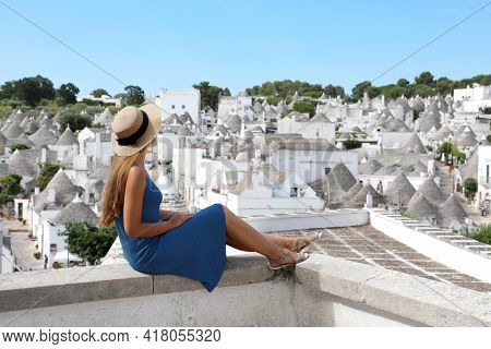 Beautiful Young Woman With Hat Sitting On Wall Looking At Stunning Panoramic View Of Alberobello Tru