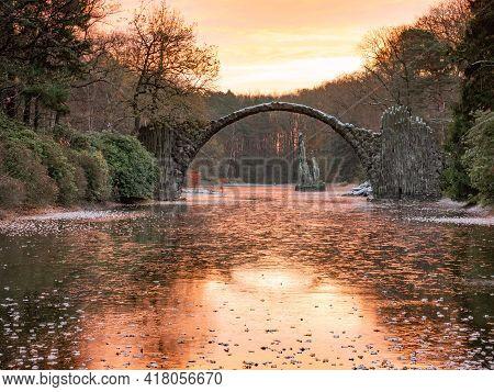 Chill Autumn Morning In Azalea And Rhododendron Park Kromlau. Round Arch Basalt Bridge Over Frozen L