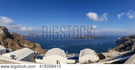 Panorama Of The Coast On The Island Of Santorini Caldera In Greece. The Background Is A Blue Sky Wit