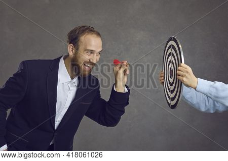 Businessman Aiming Dart At Dartboard As Metaphor For Setting Goals And Objectives