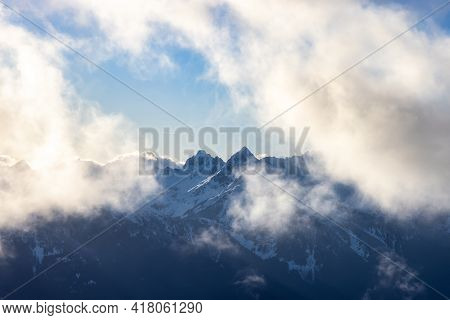 Rugged Mountain Peaks Covered In Snow And Clouds In Canadian Nature Landscape. Taken In Squamish, No