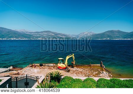 Yellow Crawler Tractor With A Bucket Works To Strengthen The Coast Near The Sea