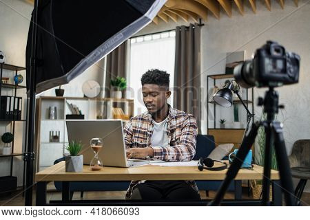 Popular Afro American Blogger Using Modern Laptop, Video Camera And Softbox For Streaming At Home. Y