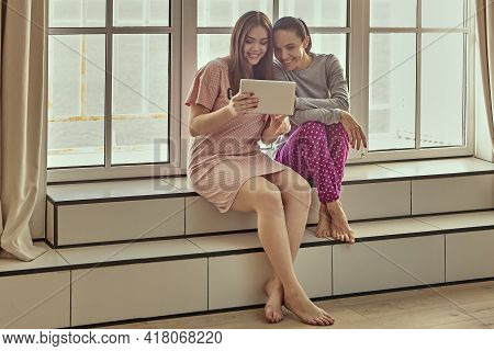 Two Women In Sleepwear Are Sitting On Windowsill And Watching Funny Video On Tablet Pc Screen.