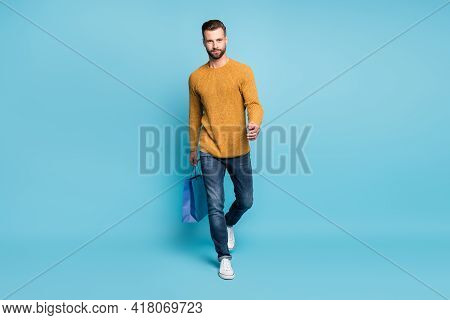 Full Sie Photo Of Young Confident Serious Handsome Man Go Walk Hold Shopping Bag Isolated On Blue Co