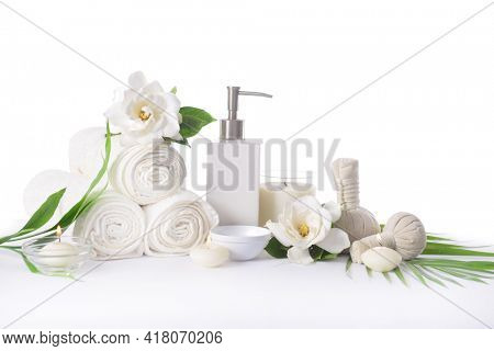 Spa setting with green palm leaves , ,bottles of essential oil  , gardenia, jasmine, herbal ball, salt in bowl ,candle , herbal ,ball