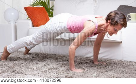 Fit Healthy Middle-aged Woman Working Out At Home Doing The Plank Pose Yoga Exercise To Strengthen A