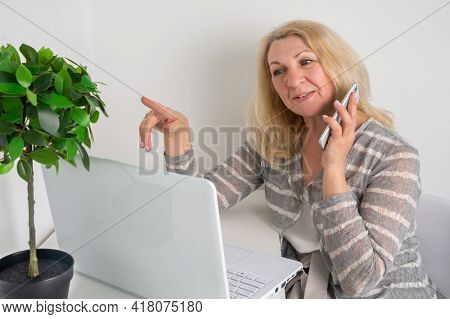 A Middle-aged Woman Sits At A Computer, Speaks On The Phone And Works Remotely. An Elderly Blonde Ma