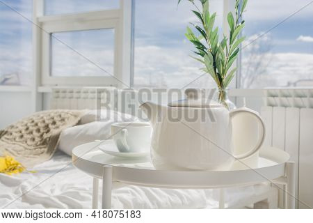 White Teapot With Tea, White Cup Stand On A White Table In The Morning In The Bedroom.