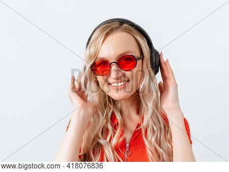 Lovely Blonde Girl Listens To Music With Wireless Headphones, Standing On A White Background. Girl W