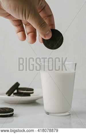 Male Hand Carrying A Chocolate Cookie To Soak It In Milk