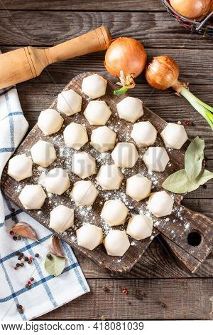 Frozen Meat Dumplings On A Wooden Board On Wooden Background. Semi-finished Products. Top View