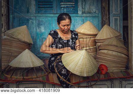 Vietnamese Old Woman Craftsman Making The Traditional Vietnam Hat In The Old Traditional House In Ap