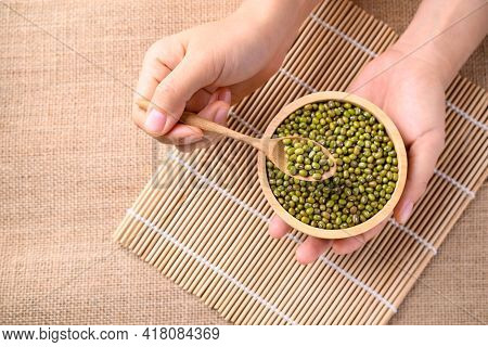 Mung Bean Seeds In Spoon With Bowl Holding By Hand, Food Ingredients In Asian Cuisine And Produce Mu