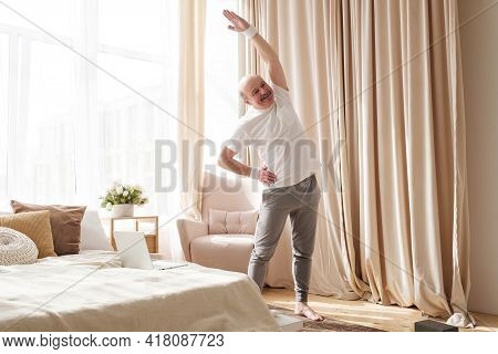 Senior Bald Man In Yoga Side Stretch Asana Doing Exercies Alone At Home.