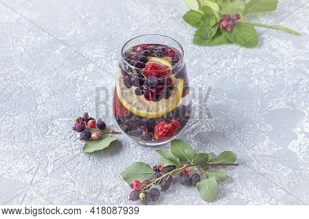 Fresh Cool Detox Drink With Berries And Lemon. Glass Of Lemonade Or Infuse Water, Tea With Leaves Mi