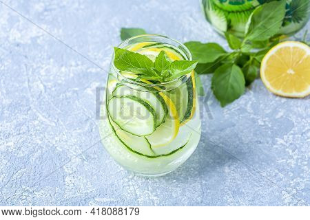Fresh Cool Detox Water Drink With Cucumber And Lemon.  Glass Of Lemonade With Basil And Mint Leaves.