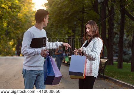 Friends Met In Park After Shopping With Paper Shopping Bags In Their Hands.