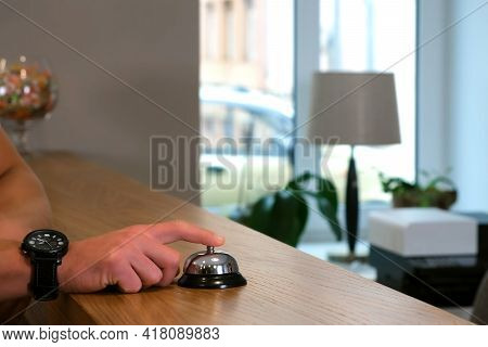 The Mans Hands Are Pressing The Bell To Call The Staff In Reception Of Hotel, Closeup Side View. Pla