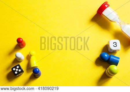 Layout Of Board Games On A Yellow Background: Dice, Chips, Hourglass Timer. Entertainment At Home Fo