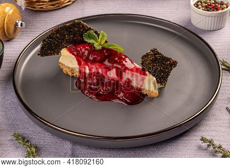 Berries Cheescake With Red Icing On Top Servod On The Restaurant Table