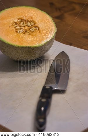 Half Cantaloupe With Seeds On Cutting Board With Knife