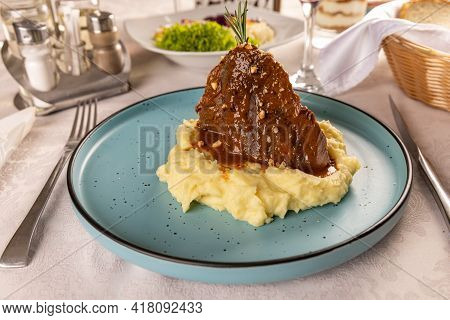 Slow Cooked Pork Served With Mashed Potatoes And Bbq Sauce