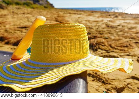 Sun Protection Accessories On Sea Shore. Yellow Straw Hat And Sunscreen Lotion On Sandy Beach. Summe