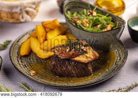 Steak With Grilled Duck Liver Served With Potato Wedges And Aragula