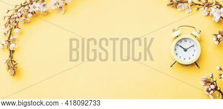 Spring Time Flowers Blossom And May Flowers With Alarm Clock On Yellow. For Banner, Branches Of Blos